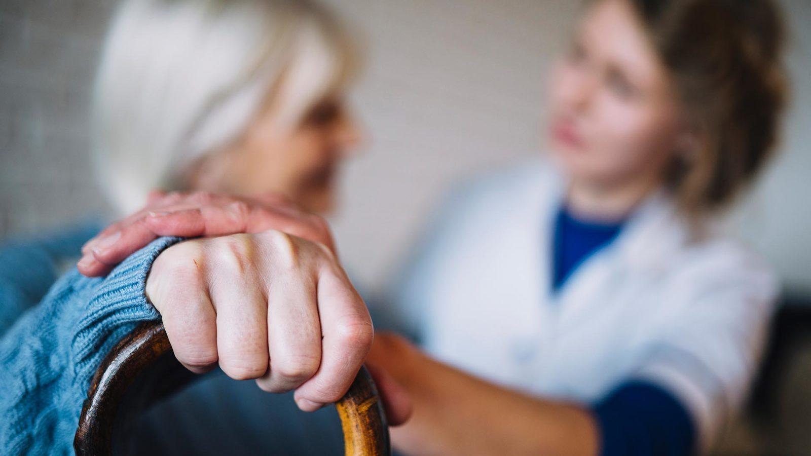 caregiver talks to an elderly woman